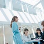 KCで地域で行う児童英語教室の教案について議論する学生とアドバイスする学習支援員